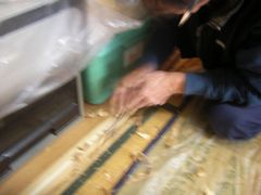 折り扉の溝を作る大工さんがノミで敷居を削る