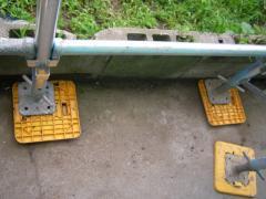 地面にプラスチック製のプレートを置いて、足場を組み立てる