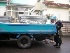 足場屋さんが足場金具をトラックから下ろす