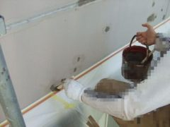 外壁がところどころ腐食している箇所に防水塗料を塗る