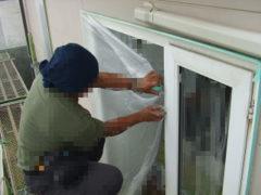 塗料がかからないように窓にビニールシートを貼る
