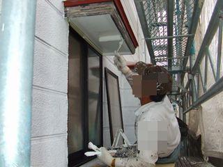 窓の庇の軒天をローラーで塗装中